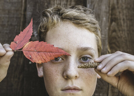 Close-up portrait of boy holding autumn leaves and pine cone against wood - CAVF24420