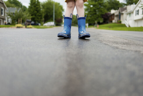 Low section of boy in rubber boots standing on wet road - CAVF24423