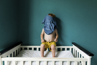 Boy hiding face with t-shirt while sitting on railing - CAVF24447