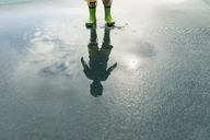Reflection of boy in rubber boots standing in puddle - CAVF24450