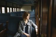 Thoughtful woman looking through window while sitting in train - CAVF24584