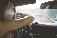 Portrait of young woman leaning on steering wheel in car - CAVF24590