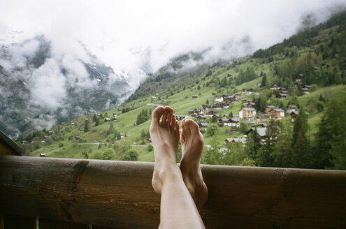 Low section of woman relaxing in balcony against mountains - CAVF24593