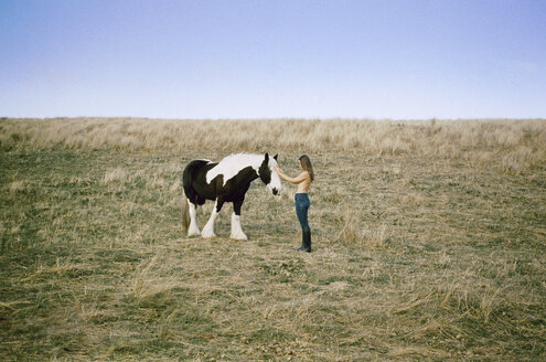 Side view of topless woman stroking horse on grassy field against clear sky - CAVF24605