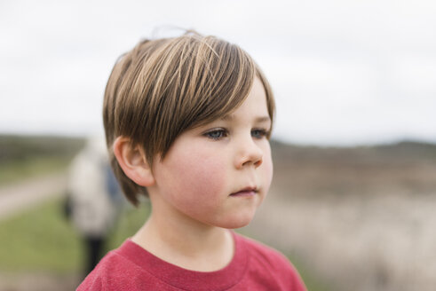 Thoughtful boy looking away while standing on field - CAVF24640