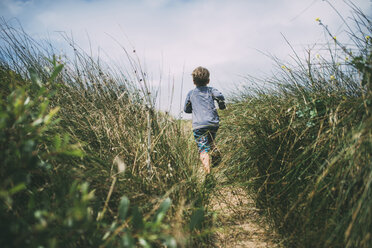 Rear view of boy running on field amidst plants at A_o Nuevo State Park - CAVF24679