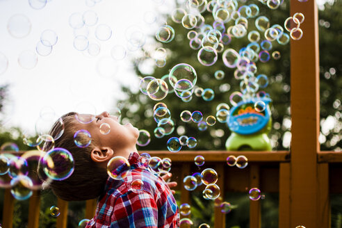 Happy boy enjoying bubbles while standing in porch - CAVF24724
