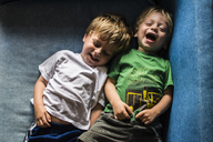 High angle view of happy brothers lying on sofa at home - CAVF24754