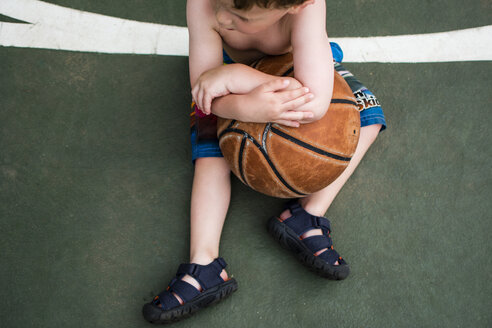 High angle view of boy holding basketball while sitting on court - CAVF24763