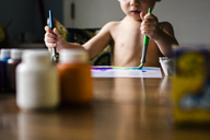 Midsection of boy painting on paper at home - CAVF24793