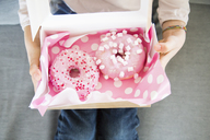 Girl holding box with doughnuts, partial view - LVF06818