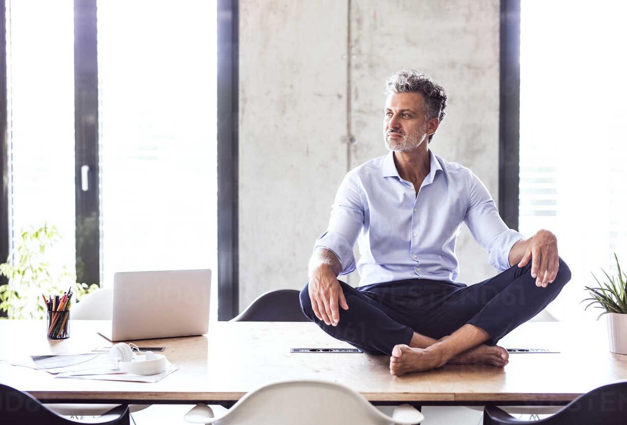 Mature businessman sitting barefoot on desk in office - HAPF02653 - HalfPoint/Westend61