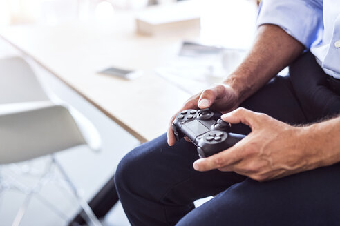 Close-up of businessman sitting on desk in office using controller - HAPF02656