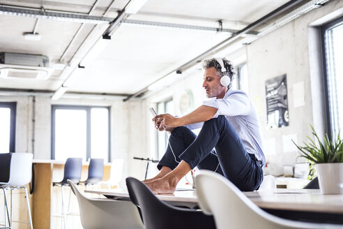 Mature businessman with smartphone and headphones sitting barefoot on desk in office - HAPF02659