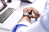Close-up of businessman at desk with laptop using smartwatch - HAPF02665