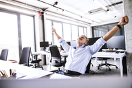 Happy mature businessman sitting at desk in office raising his arms - HAPF02677
