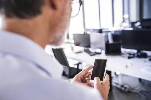 Close-upof businessman in office using smartphone - HAPF02689