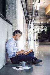 Mature businessman sitting on the floor using tablet - HAPF02698