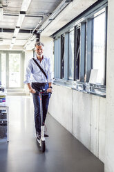 Portrait of happy mature businessman riding scooter in office - HAPF02704