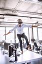 Barefoot mature businessman on desk in office wearing VR glasses - HAPF02710
