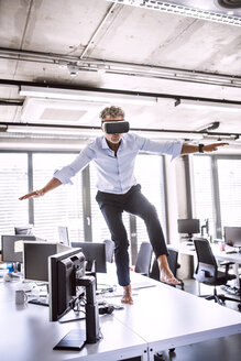 Barefoot mature businessman on desk in office wearing VR glasses - HAPF02710