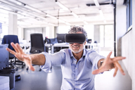 Happy mature businessman wearing VR glasses in office - HAPF02716