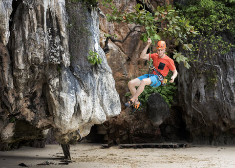 Thailand, Krabi, Lao Liang, climber abseiling from rock wall - ALRF01021