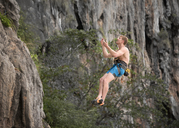 Thailand, Krabi, Lao Liang, barechested climber abseiling from rock wall - ALRF01036