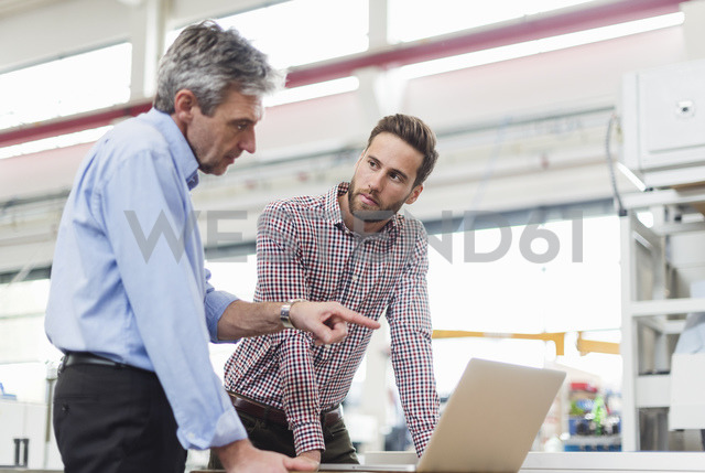 Businessmen using laptop in production hall - DIGF03485