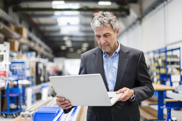 Businessman using laptop in production hall - DIGF03494