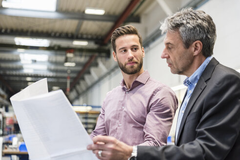 Businessmen with plan during meeting in production hall - DIGF03497