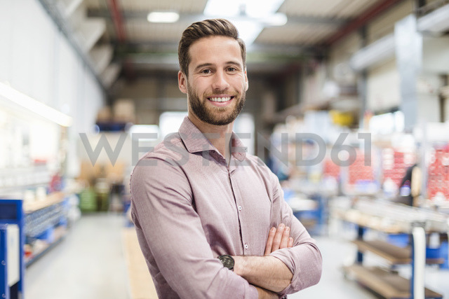 Smiling businessman in production hall - DIGF03503