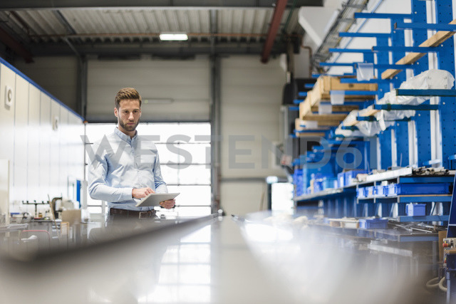 Businessman using tablet in production hall - DIGF03506