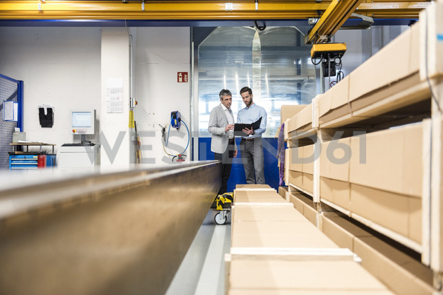 Businessmen during meeting with clipboard in storage - DIGF03512