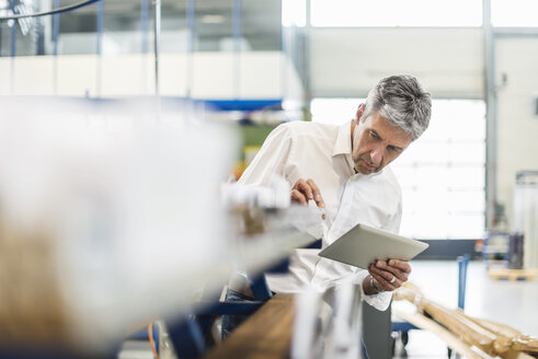 Businessman using tablet in production hall - DIGF03515