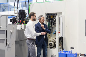 Businessmen looking at machine in factory - DIGF03527