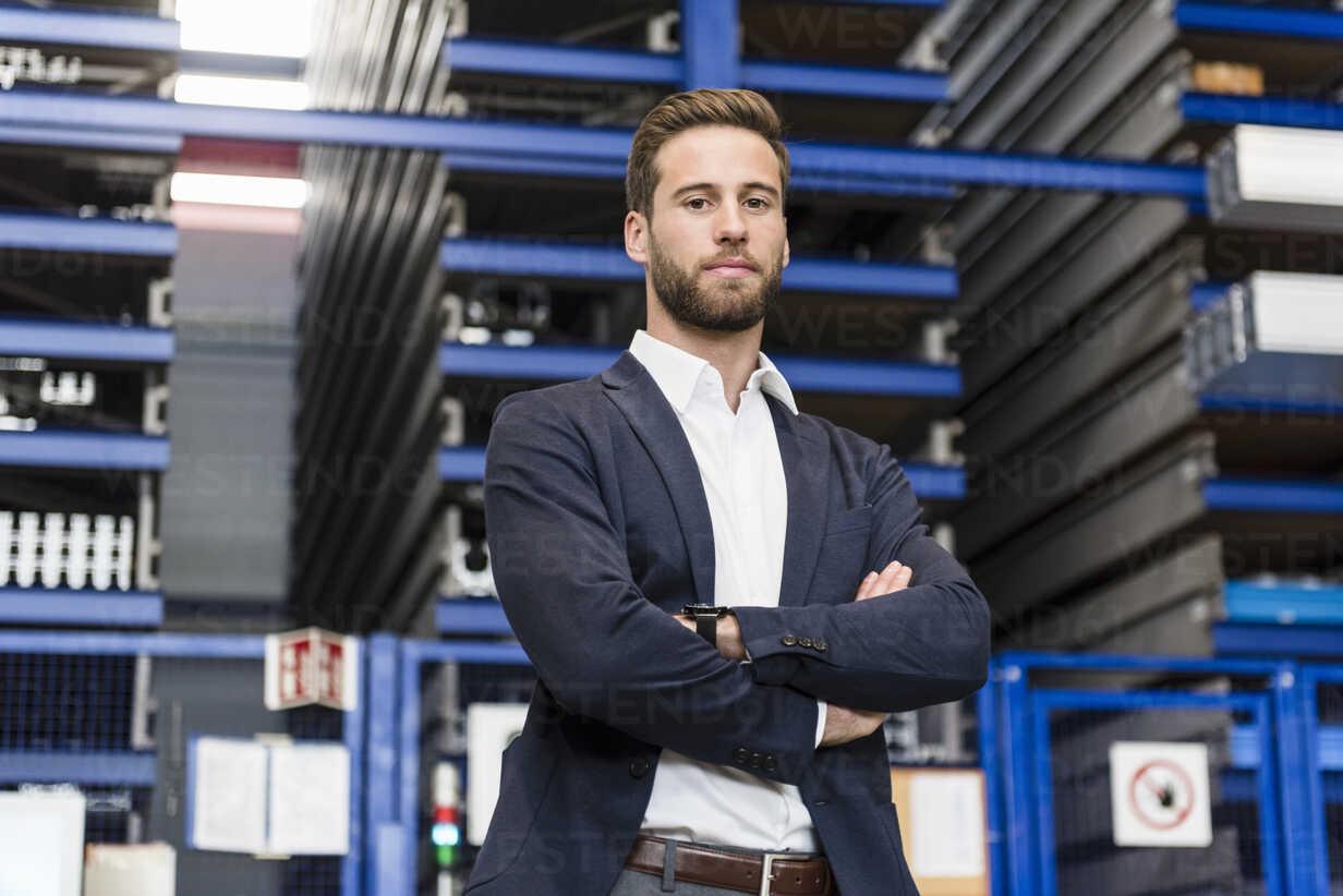 Smiling businessman in storage - DIGF03530 - Daniel Ingold/Westend61