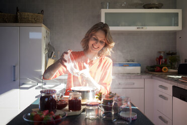 Smiling woman making strawberry jam in kitchen at home - MOEF00933