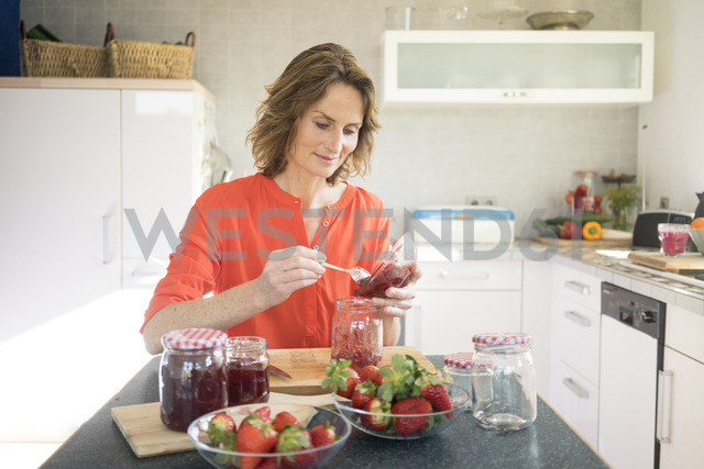 Woman making strawberry jam in kitchen at home - MOEF00936