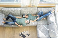 Happy mature couple lying on couch at home wearing VR glasses - MOEF00939