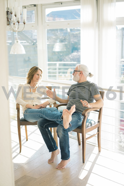 Relaxed mature couple talking on chairs at home - MOEF00942