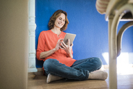 Smiling woman sitting on the floor at home using tablet - MOEF00948