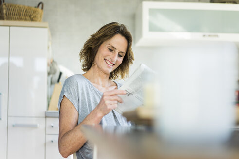 Smiling woman reading newspaper in kitchen at home - MOEF00951