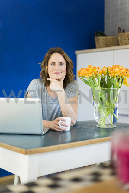 Portrait of smiling woman with laptop in kitchen at home - MOEF00957