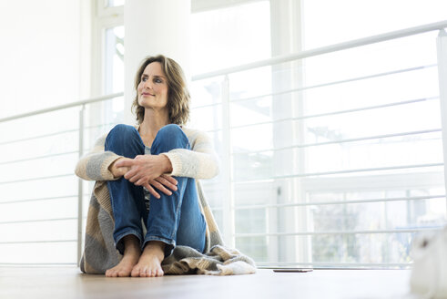 Relaxed woman sitting on the floor at home - MOEF00963