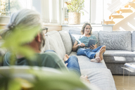 Mature couple relaxing on couch at home with woman holding tablet - MOEF00966