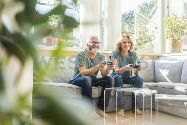 Happy mature couple sitting on couch at home playing video game - MOEF00969