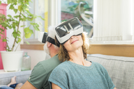 Mature couple sitting on couch at home wearing VR glasses - MOEF00972