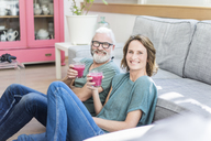 Happy mature couple with healthy drinks in living room at home - MOEF00975