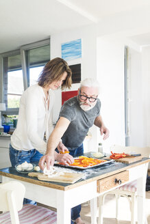 Mature couple preparing a pizza in kitchen at home - MOEF00984